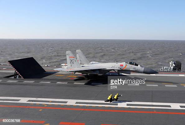 This picture taken on an undisclosed date in December 2016 shows a Chinese J15 fighter jet preparing to take off from the deck of the Liaoning...