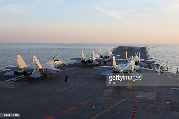 This picture taken on an undisclosed date in December 2016 shows Chinese J15 fighter jets waiting on the deck of the Liaoning aircraft carrier during...
