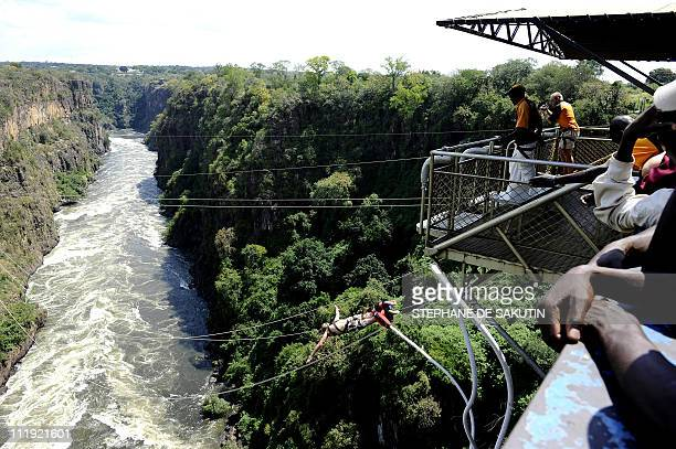 This picture taken on April 1 2011 shows people watching a man bungee jumping in Victoria Falls Zimbabwe Zimbabwe's tourism earnings jumped 47...