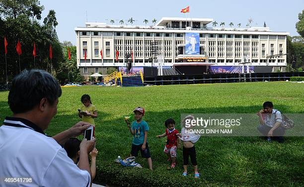 This picture taken on April 10 2015 shows a man taking a family photo in front of the former presidential palace of the former South Vietnam USbacked...