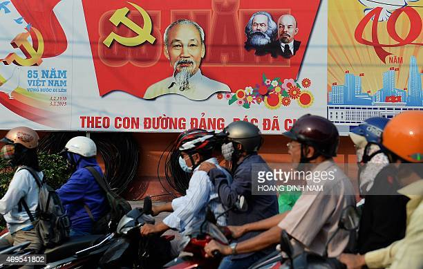 This picture taken on April 10 2015 shows motorcyclists riding past propaganda billboards marking the 40th anniversary of the end of the Vietnam War...