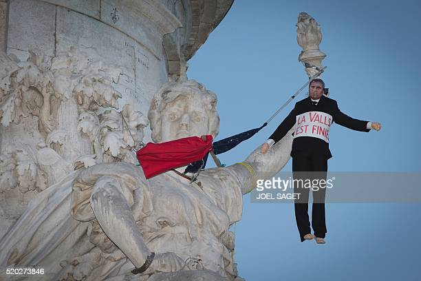 This picture taken on April 10 2016 shows a dummy representing French Prime Minister Manuel Valls hanged to the 'Statue of the Republic' during the...