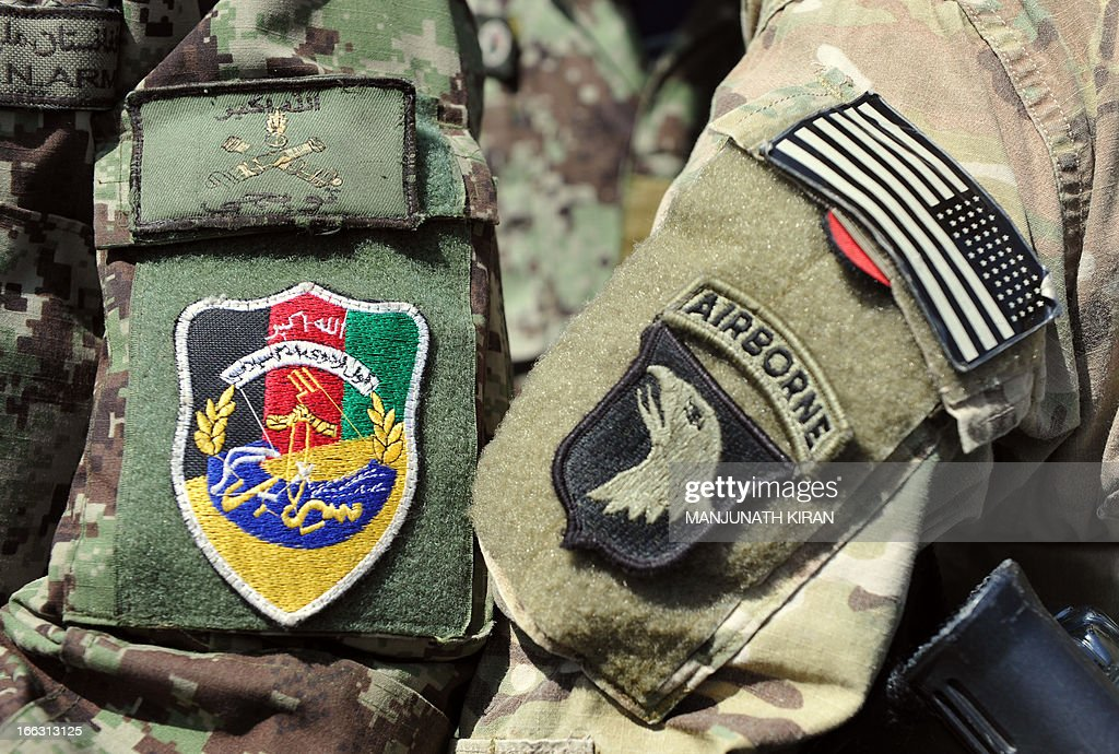 This picture taken on April 11, 2013 shows the badges of a US soldier of Combined Team Bastogne (Nangarhar), 1st Brigade Combat Team, 101st Airborne Division (Air Assault) (R) and of a soldier of the Field Artillery Division of the Afghan National Army (ANA) (L) on their arms as they stand next to each other during a training session of ANA soldiers at the US Shinwar Forward Base in the province of Nangarhar. The US Field Artillery Battery of 4th Kandak is training Afghan soldiers in using artillery to support their Afghan National Army. AFP PHOTO / MANJUNATH KIRAN