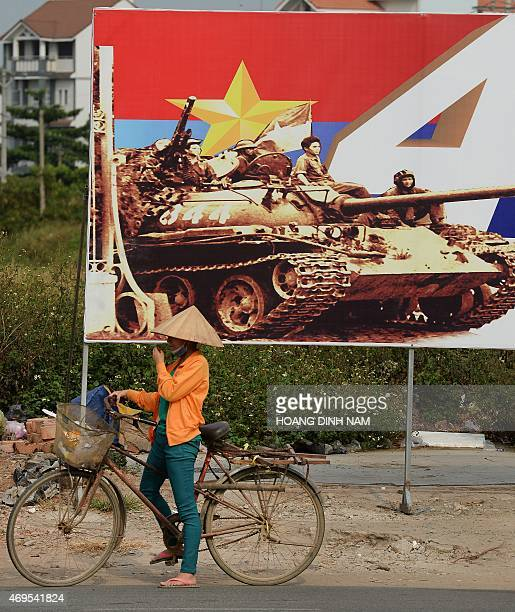 This picture taken on April 11 2015 shows a cyclist next to a billboard featuring the 40th anniversary of the communist victory over the former South...