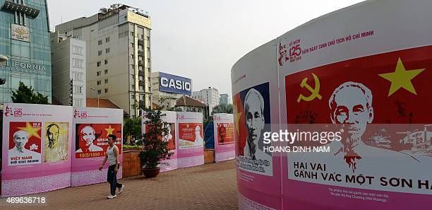 This picture taken on April 11 2015 shows a man walking past posters featuring portraits of late president Ho Chi Minh founder of today's communist...