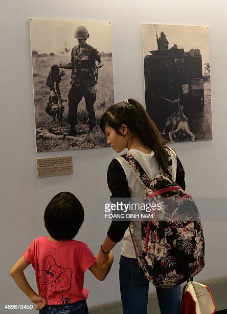 This picture taken on April 11 2015 shows an young girl looking at photographs of massacre scenes committed by US soldiers during the Vietnam War as...