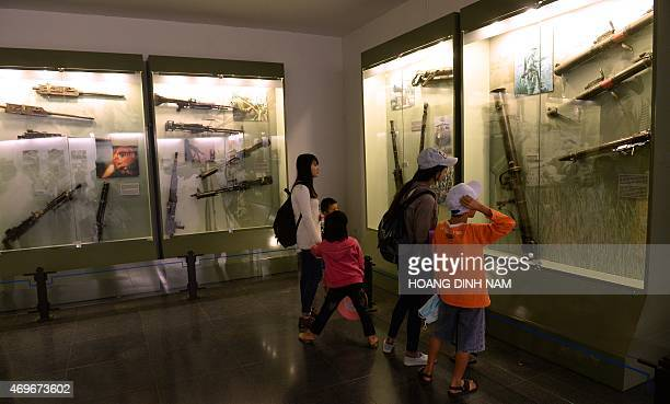 This picture taken on April 11 2015 shows local visitors looking at different USmade weapons used during the Vietnam War as they tour the War Relics...