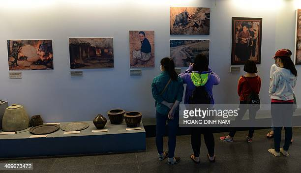 This picture taken on April 11 2015 shows visitors looking at photographs of massacre scenes committed by US soldiers during the Vietnam War as they...