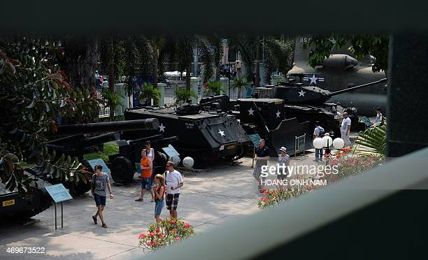 This picture taken on April 11 2015 shows visitors walking past tanks canons used by US troops and USbacked southern Vietnam's army during the...
