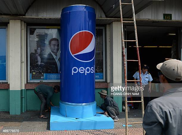 This picture taken on April 11 2015 shows workers installing a model of a can to advertise US soft drink maker Pepsi in downtown Ho Chi Minh City The...