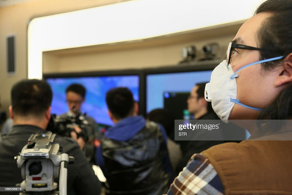 This picture taken on April 13, 2013 shows a journalist (R) wearing a mask while attending a press conference on the current conditions after Beijing reported its first human case of H7N9 bird flu at a hospital in Beijing. China's H7N9 bird flu virus spread to a new province on April 14, with state media reporting two human cases in central Henan just west of the area where the disease has been centred. Until April 13, when one case was reported in the capital of Beijing, all other instances had occurred in the eastern city of Shanghai and nearby Zhejiang, Jiangsu and Anhui provinces hundreds of miles (kilometres) away. CHINA OUT AFP PHOTO