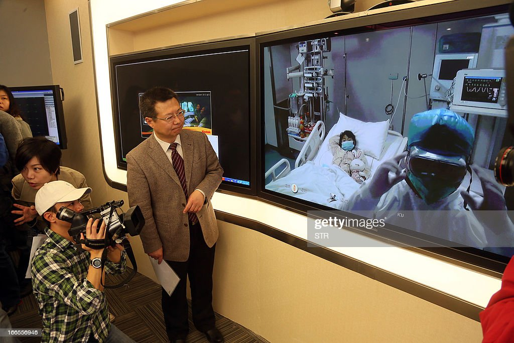 This picture taken on April 13, 2013 shows vice president of Beijing's Ditan hospital Cheng Jun (2nd L) standing next to a video screen showing Beijing's first human case of H7N9 bird flu, a 7-year-old girl (C) lying in her bed in an ICU at Ditan hospital, broadcast at a press conference to update the situation on the disease in the Chinese capital. China's H7N9 bird flu virus spread to a new province on April 14, with state media reporting two human cases in central Henan just west of the area where the disease has been centred. Until April 13, when one case was reported in the capital of Beijing, all other instances had occurred in the eastern city of Shanghai and nearby Zhejiang, Jiangsu and Anhui provinces hundreds of miles (kilometres) away. CHINA OUT AFP PHOTO