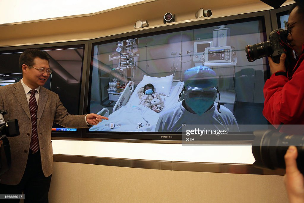 This picture taken on April 13, 2013 shows vice president of Beijing's Ditan hospital Cheng Jun ( L) standing next to a video screen showing Beijing's first human case of H7N9 bird flu, a 7-year-old girl (C) lying in her bed in an ICU at Ditan hospital, broadcast at a press conference to update the situation on the disease in the Chinese capital. China's H7N9 bird flu virus spread to a new province on April 14, with state media reporting two human cases in central Henan just west of the area where the disease has been centred. Until April 13, when one case was reported in the capital of Beijing, all other instances had occurred in the eastern city of Shanghai and nearby Zhejiang, Jiangsu and Anhui provinces hundreds of miles (kilometres) away. CHINA