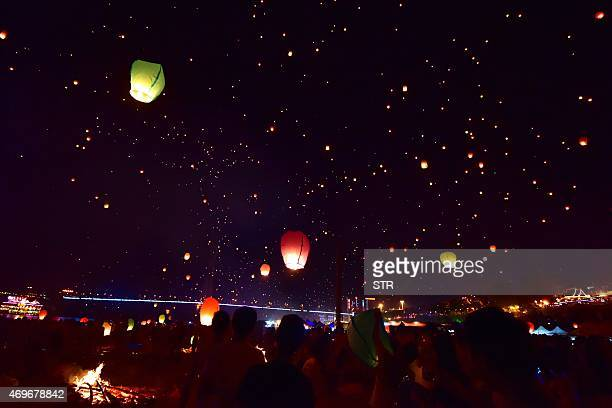 This picture taken on April 13 2015 shows people flying sky lanterns into the sky to celebrate the Dai minority group new year in Xishuangbanna...
