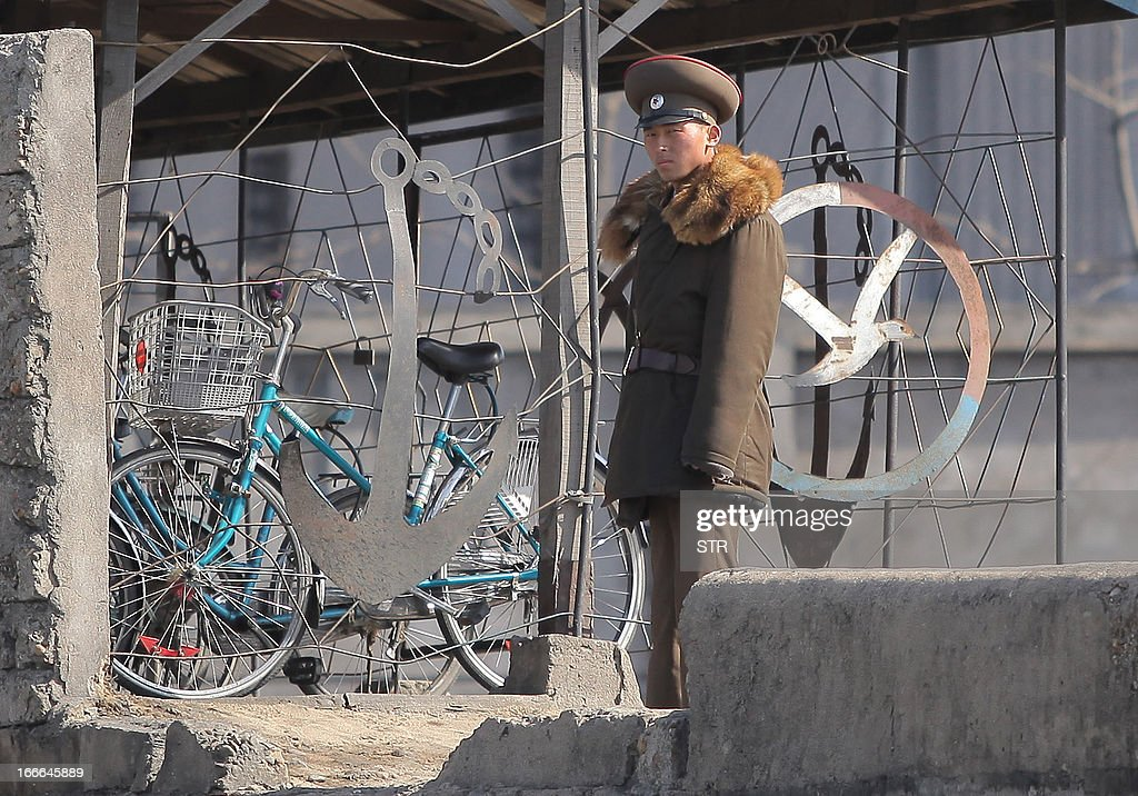 This picture taken on April 14, 2013 shows a North Korean soldier patrols along the bank of the Yalu River in the North Korean town of Sinuiju across from the Chinese city of Dandong. US Secretary of State John Kerry said he would be prepared to reach out to Pyongyang urging it back to negotiations, as he vowed Washington would protect Japan from North Korea's threats. CHINA