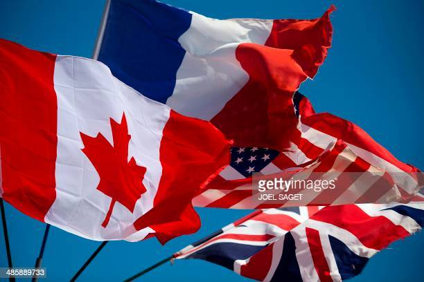 This picture taken on April 15 2014 shows British French US and Canadian flags in Ouistreham northern France AFP PHOTO / JOEL SAGET