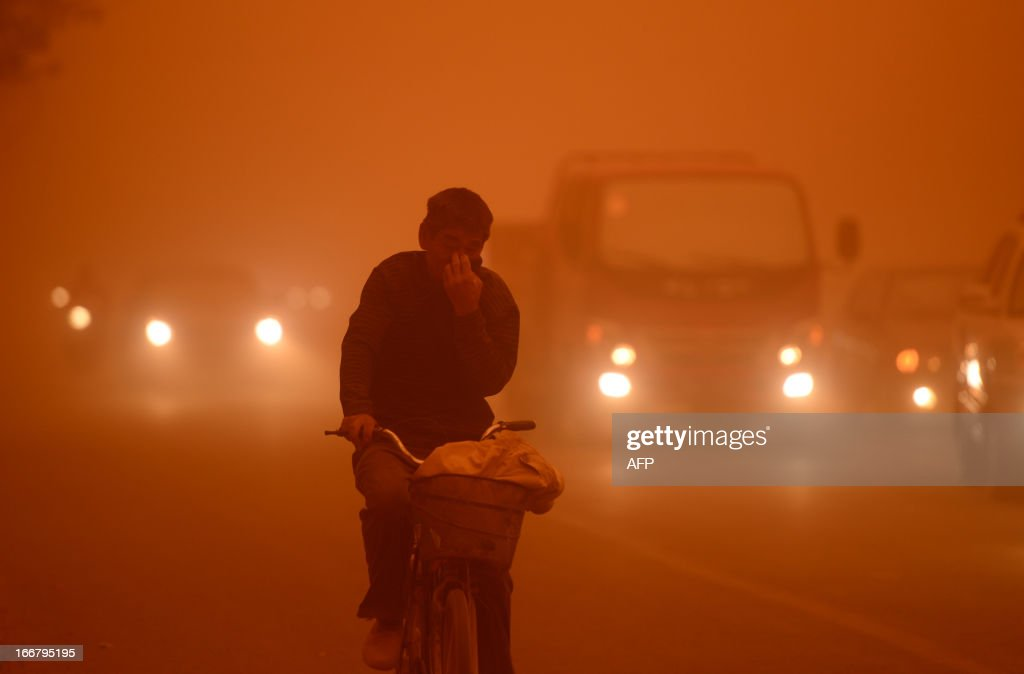 This picture taken on April 16, 2013 shows a man riding a bike during a heavy sandstorm in Yecheng county, northwest China's Xinjiang Uygur Autonomous Region. The sandstorm affected several cities including Kashi, Hetian and Kezhou. CHINA OUT AFP PHOTO