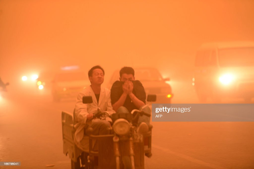 This picture taken on April 16, 2013 shows commuters travelling on a pedicab during a heavy sandstorm in Yecheng county, northwest China's Xinjiang Uygur Autonomous Region. The sandstorm affected several cities including Kashi, Hetian and Kezhou. CHINA OUT AFP PHOTO