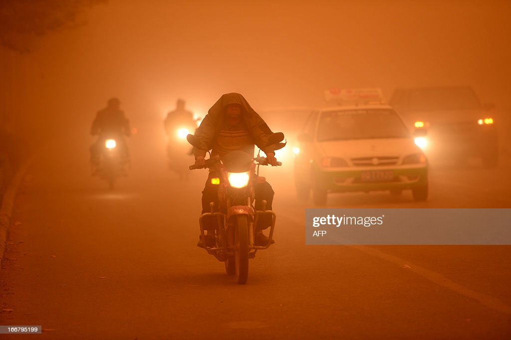 This picture taken on April 16, 2013 shows motorists driving with their lights during a heavy sandstorm in Yecheng county, northwest China's Xinjiang Uygur Autonomous Region. The sandstorm affected several cities including Kashi, Hetian and Kezhou. CHINA OUT AFP PHOTO