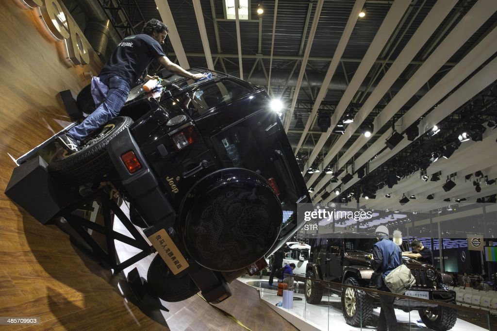 This picture taken on April 19, 2014 shows a staff installing a Jeep car model in an exhibition hall of the China International Exhibition Center , ahead of the 'Auto China 2014' Beijing International Automotive Exhibition in Beijing. Leading automakers are gathering in Beijing for the kickoff of China's biggest car show, but lackluster growth and environmental restrictions in the world's largest car market have thrown uncertainty into the mix. More than 1,100 vehicles are being showcased at the auto show, which opens to the public on April 21. CHINA