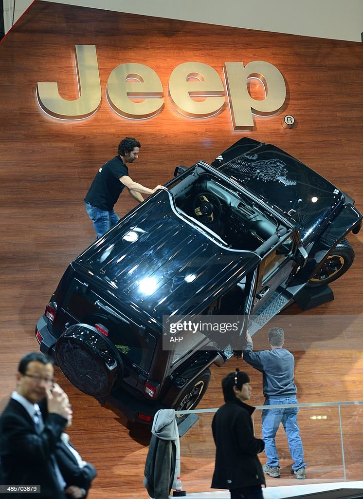 This picture taken on April 19, 2014 shows staff installing a Jeep car model in an exhibition hall of the China International Exhibition Center ahead of the 'Auto China 2014' Beijing International Automotive Exhibition in Beijing. Leading automakers are gathering in Beijing for the kickoff of China's biggest car show, but lackluster growth and environmental restrictions in the world's largest car market have thrown uncertainty into the mix. More than 1,100 vehicles are being showcased at the auto show, which opens to the public on April 21. CHINA