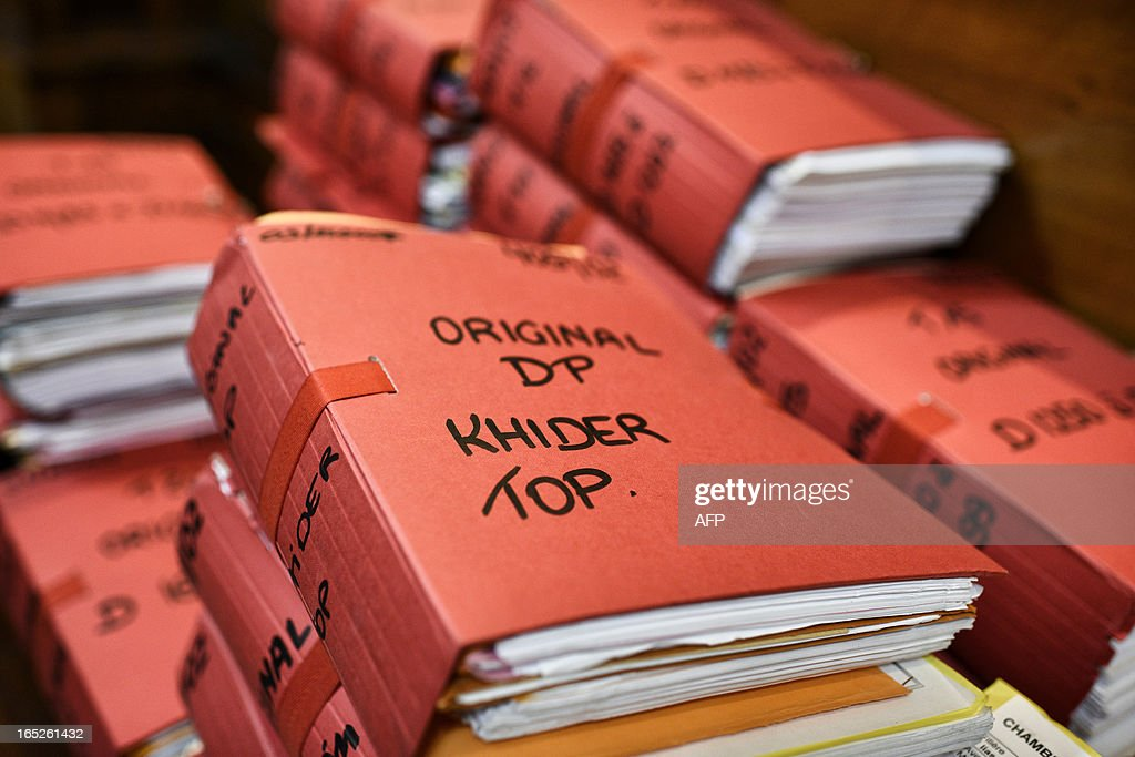 This picture taken on April 2, 2013 shows folders in the courtroom of Lyon's criminal court, on the opening day of Christophe Khider and Omar Top El Hadj's trial. They are judged for having escaped from jail using explosives and taking hostages two prison staffs. AFP PHOTO / JEFF PACHOUD