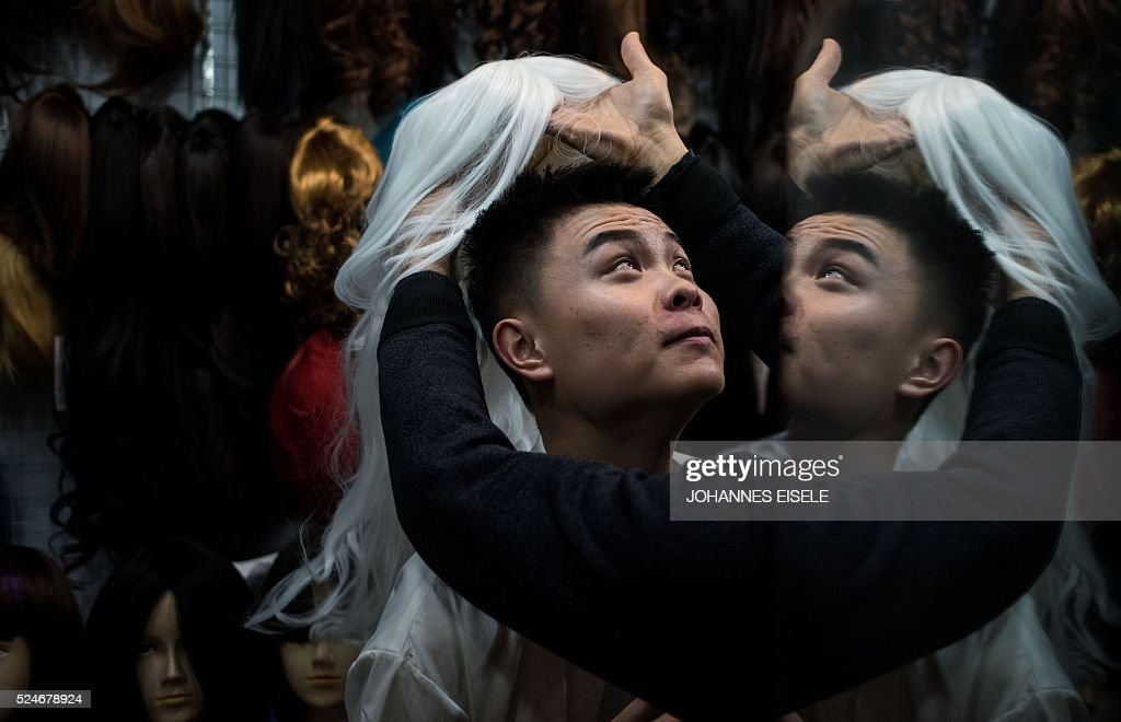 This picture taken on April 2, 2016, shows Yu Xiaoyang - who uses the stage name Xiao Bai meaning 'Little White' - trying on a periwig during a shopping tour with his friends in Shanghai. In a bouffant blonde wig and outsize eyelashes, Yu Xiaoyang flamboyantly parades across a Shanghai stage, his fake breasts filling his skintight golden jumpsuit. Yu was among 20 contestants taking part in a cross-dressing competition in China's commercial hub. the contry only decriminalised homosexuality in 1997 and discrimination is common, although tolerance is greater in major cities, and the Shanghai Pride group mounts an annual series of events for the lesbian, gay, bisexual and transgender (LGBT) community and their supporters. / AFP / JOHANNES