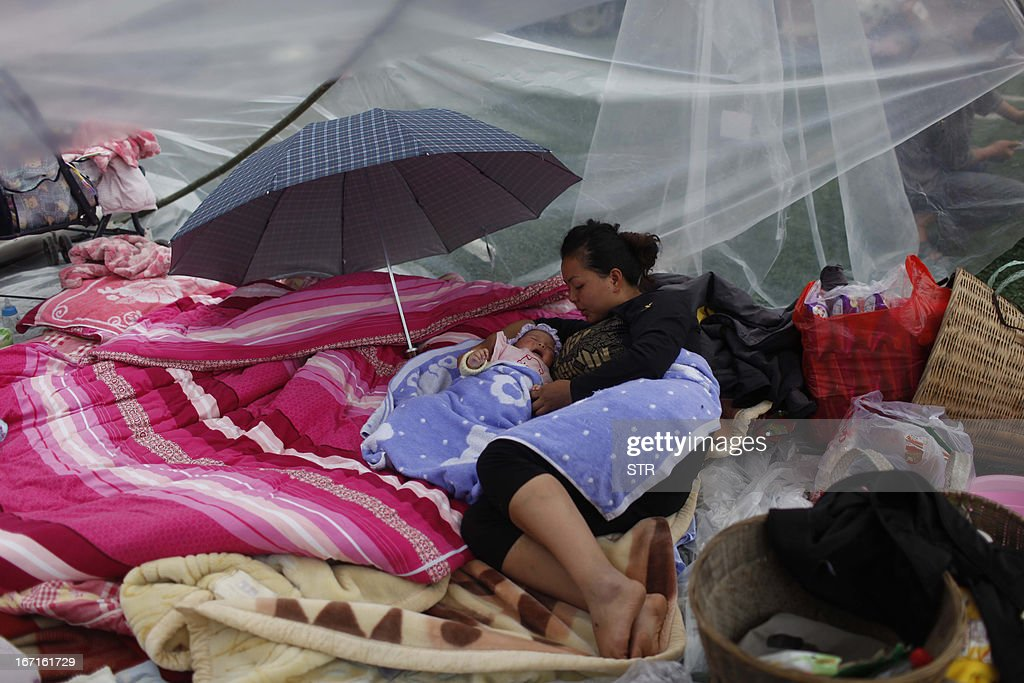 This picture taken on April 21, 2013 shows a woman and her baby resting at an emergency relief center two days after an earthquake hit, in Ya'an City, southwest China's Sichuan province. Thousands of rescue workers combed through flattened villages in southwest China in a race to find survivors from a powerful quake as the toll of dead and missing rose past 200. CHINA