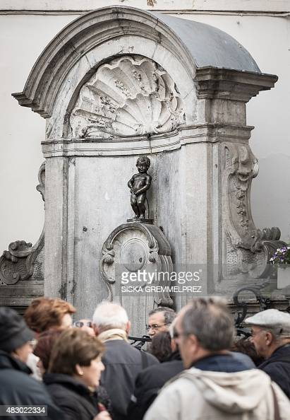 This picture taken on April 22 2014 shows people standing near Brussels' emblematic Manneken Pis statue The Belgian capital's emblematic Manneken Pis...