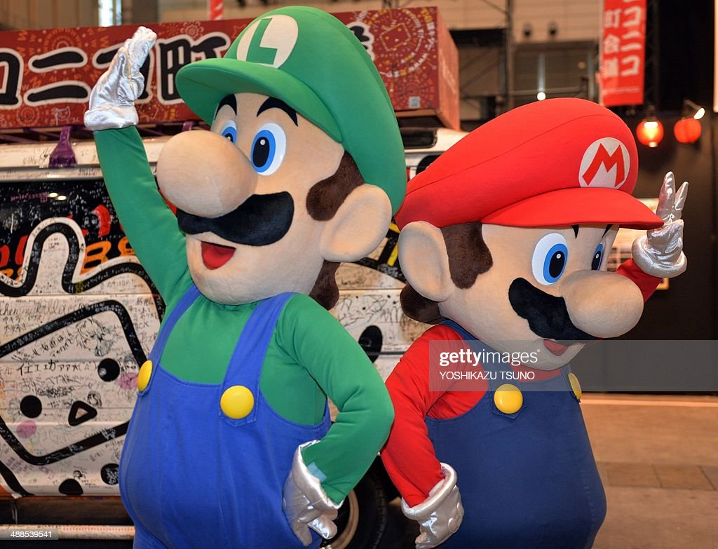 This picture taken on April 26, 2014 shows Japanese videogame giant Nintendo's characters Super Mario and Luigi (L) performing in Chiba, suburban Tokyo. Nintendo booked a 229 million USD annual loss on May 7, reversing a year-earlier profit as dismal sales of its Wii U console during the crucial Christmas holiday period dented results. AFP PHOTO / Yoshikazu TSUNO