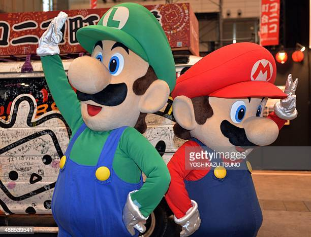 This picture taken on April 26 2014 shows Japanese videogame giant Nintendo's characters Super Mario and Luigi performing in Chiba suburban Tokyo...