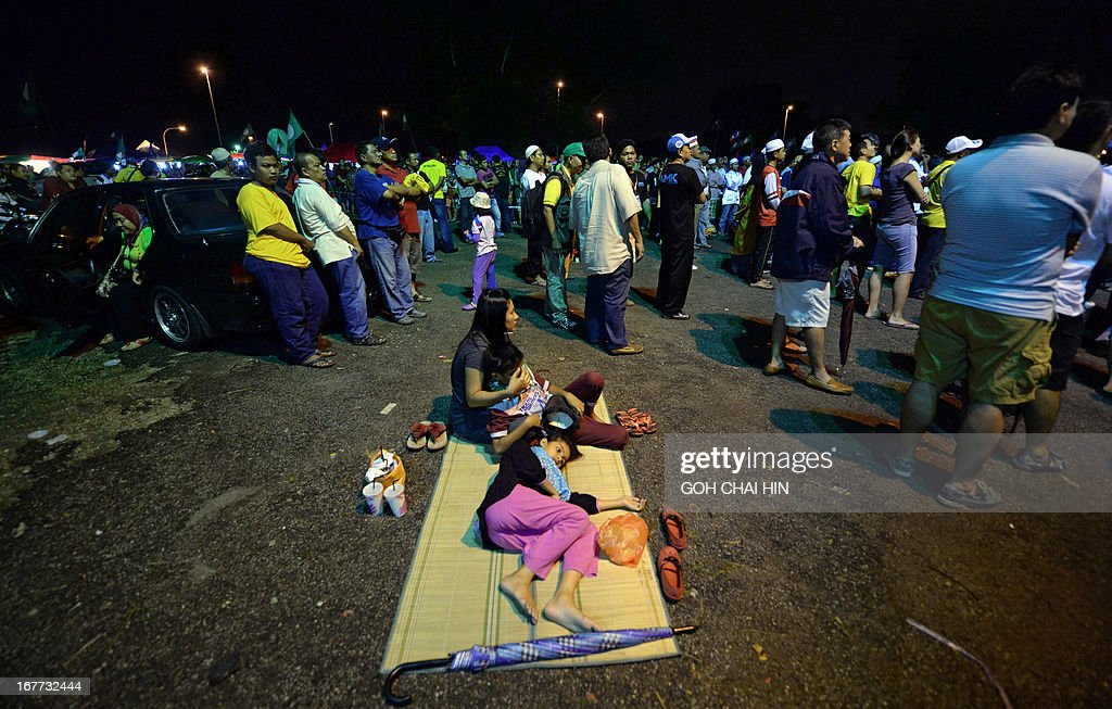 This picture taken on April 28, 2013 shows a Malay family resting amongst the crowd as they wait for the arrival of opposition leader Anwar Ibrahim during an election rally in Sungai Buloh. Anwar Ibrahim holds a slight edge over Malaysian premier Najib Razak ahead of a hotly anticipated election showdown on May 5, according to the latest opinion poll on April 26.