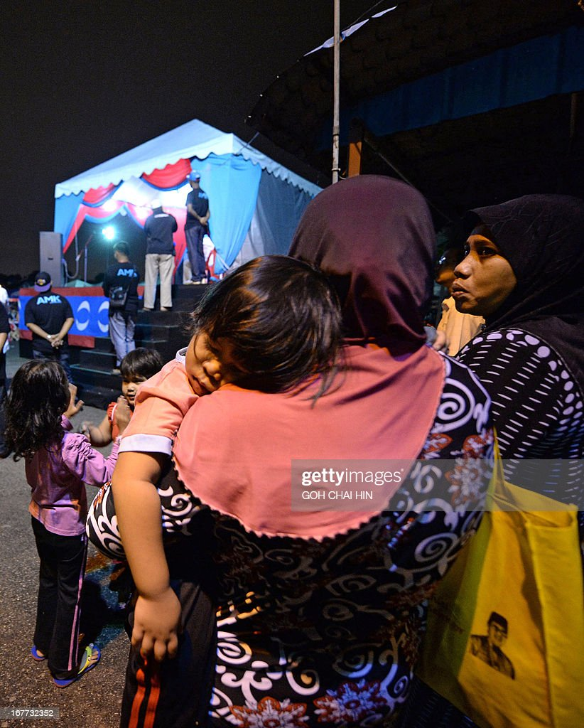 This picture taken on April 28, 2013 shows a Malay woman holding her sleeping child as she waits for the arrival of opposition leader Anwar Ibrahim during an election rally in Sungai Buloh. Anwar Ibrahim holds a slight edge over Malaysian premier Najib Razak ahead of a hotly anticipated election showdown on May 5, according to the latest opinion poll on April 26. AFP PHOTO / GOH CHAI HIN