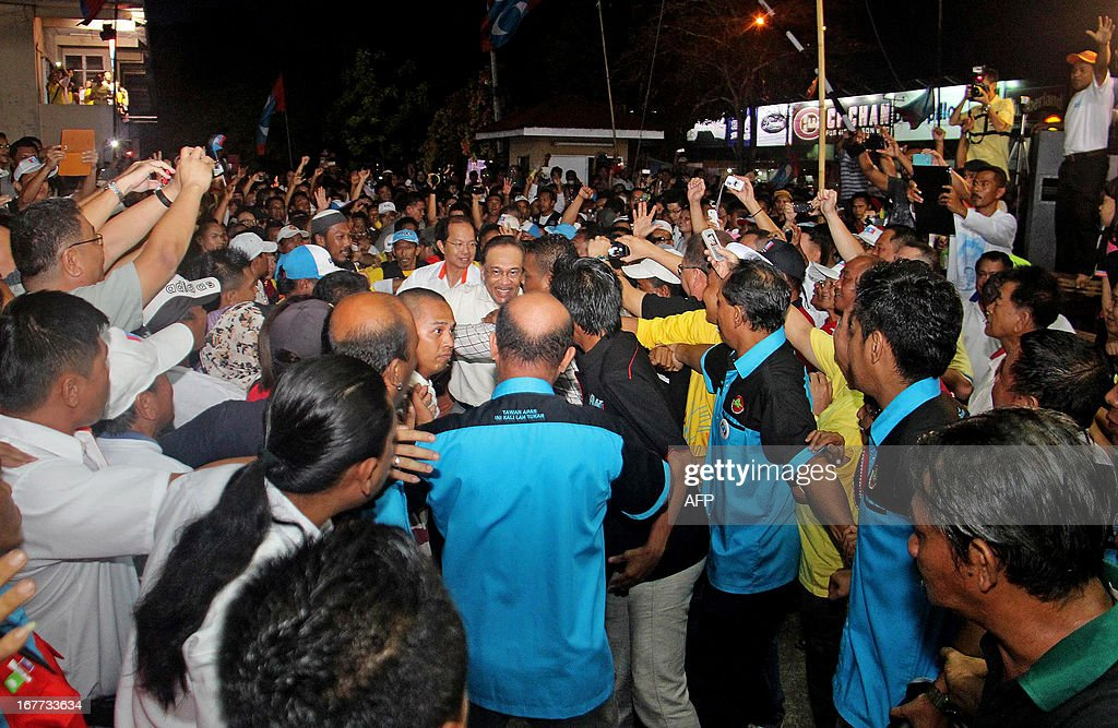 This picture taken on April 28, 2013 shows Malaysia's opposition leader Anwar Ibrahim (C) surrouned by supporters during a campaign event ahead of the country's 13th general elections in Tawau, on the southeast coast of Sabah, on the island of Borneo. Opposition leader Anwar Ibrahim held a slight edge in support over Malaysian Premier Najib Razak, according to a survey released on April 26 ahead of a hotly anticipated election showdown on May 5.