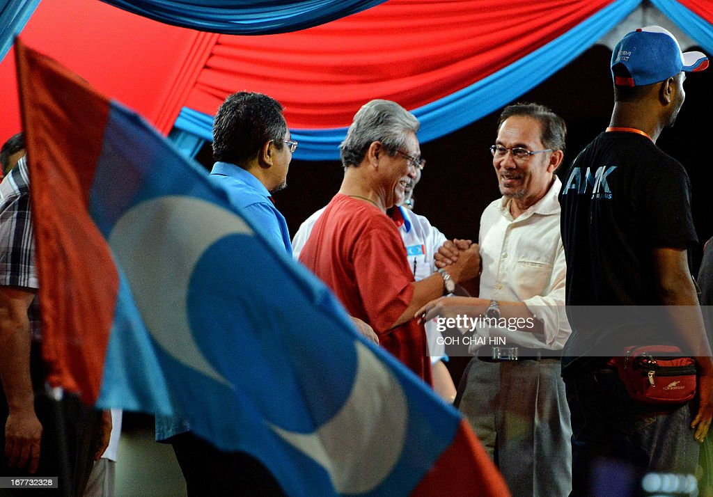 This picture taken on April 28, 2013 shows opposition leader Anwar Ibrahim (2nd R) greeting his coalition candidates during an election rally in Sungai Buloh. Anwar Ibrahim holds a slight edge over Malaysian premier Najib Razak ahead of a hotly anticipated election showdown on May 5, according to the latest opinion poll on April 26.