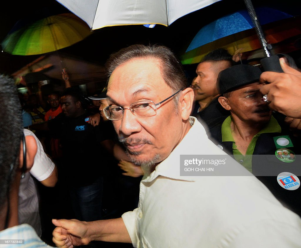 This picture taken on April 28, 2013 shows opposition leader Anwar Ibrahim making his way through the crowd as he arrives to address an election rally in Sungai Buloh. Anwar Ibrahim holds a slight edge over Malaysian premier Najib Razak ahead of a hotly anticipated election showdown on May 5, according to the latest opinion poll on April 26.