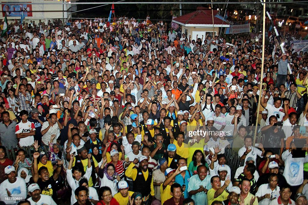 This picture taken on April 28, 2013 shows supporters listening and shouting slogans as Malaysia's opposition leader Anwar Ibrahim (not pictured) speaks during a campaign event ahead of the country's 13th general elections in Tawau, on the southeast coast of Sabah, on the island of Borneo. Opposition leader Anwar Ibrahim held a slight edge in support over Malaysian Premier Najib Razak, according to a survey released on April 26 ahead of a hotly anticipated election showdown on May 5.