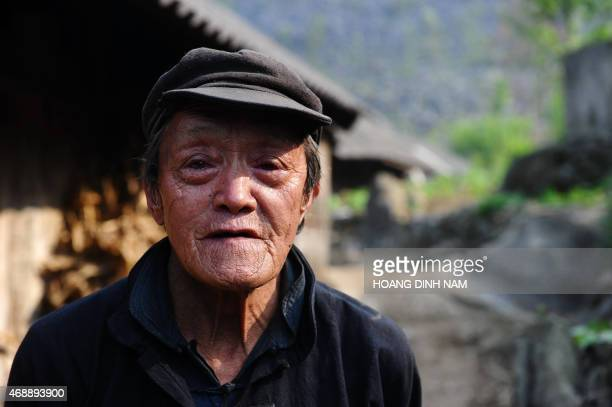 This picture taken on April 3 2015 shows an elderly H'mong ethnic man standing next to his home at Meo Vac district in the northern mountainous...