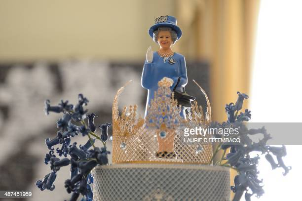 This picture taken on April 30 2014 shows a statuette portraying Queen Elizabeth II on top of a birthday cake at a birthday party in honor of the...