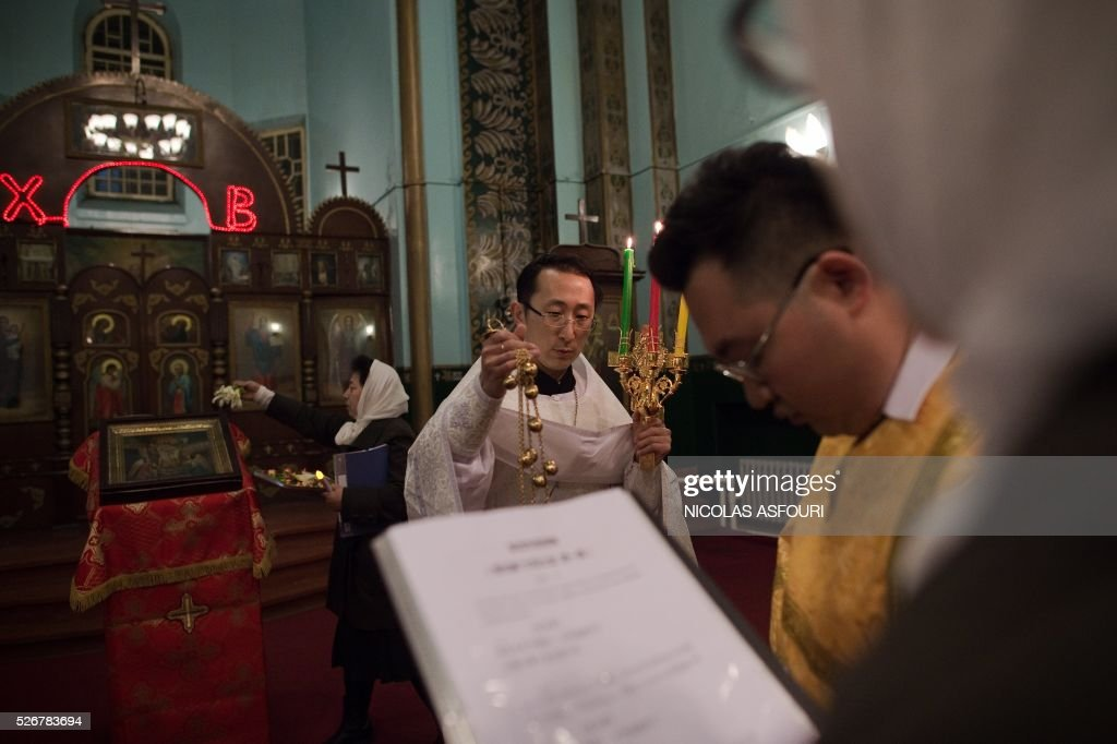 This picture taken on May 1, 2016 shows Chinese Priest Alexander Yu Shi (C) during the Easter vigil service inside the Pokrov Orthodox church in Harbing. Shi is the first Chinese Priest ordained by Russian Orthodox Church for 60 years, and is also the first ever Orthodox Priest recognised by the Chinese Communist Party.