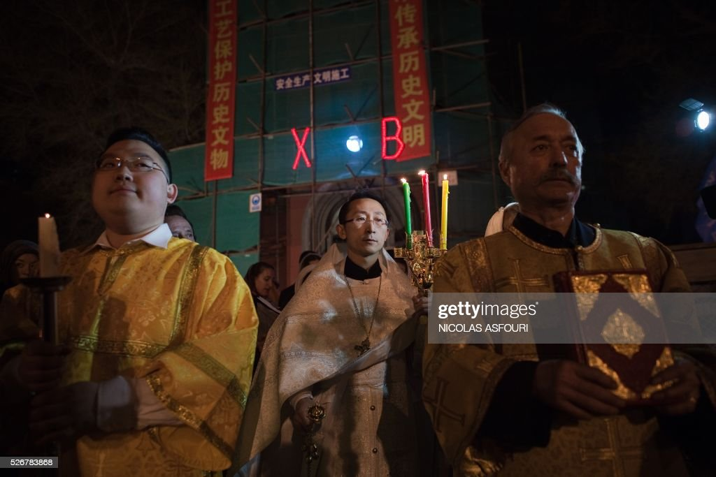 This picture taken on May 1, 2016 shows Chinese Priest Alexander Yu Shi (C) during the Easter vigil service outside the Pokrov Orthodox church in Harbing. Shi is the first Chinese Priest ordained by Russian Orthodox Church for 60 years, and is also the first ever Orthodox Priest recognised by the Chinese Communist Party.