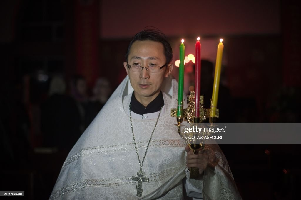 This picture taken on May 1, 2016 shows Chinese Priest Alexander Yu Shi during the Easter vigil service inside a Catholic church in Harbing. Shi is the first Chinese Priest ordained by Russian Orthodox Church for 60 years, and is also the first ever Orthodox Priest recognised by the Chinese Communist Party.
