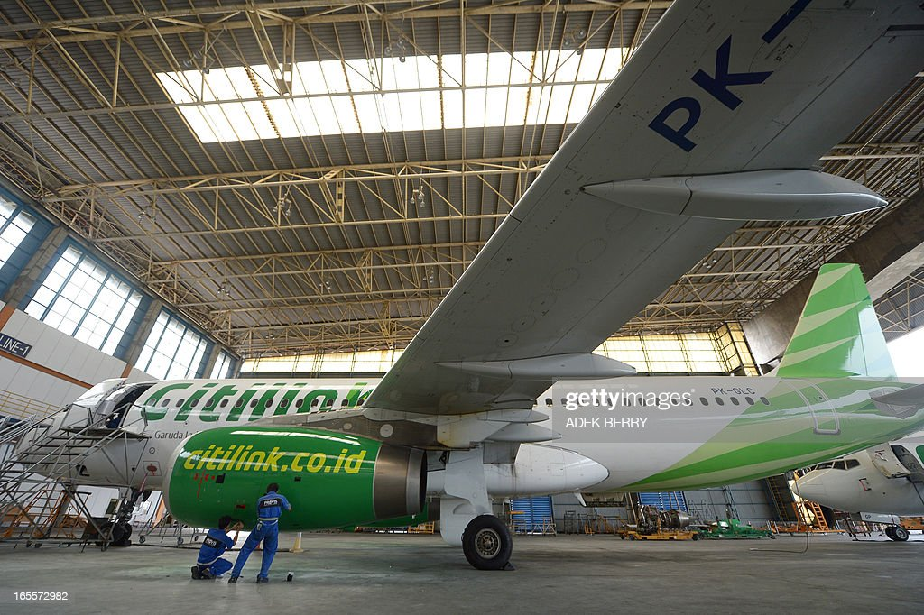 This picture taken on April 4, 2013 in Tangerang shows Indonesian technicians from GMF (Garuda Maintenance Facilities), a subsidiary of national carrier Garuda Indonesia maintaining a Citilink, a low-cost carrier of Garuda Indonesia at the Sukarno-Hatta airport in Tangerang. A new rivalry between the world's biggest planemakers is heating up in Indonesia after a record deal for Airbus in a market with huge potential that until now has been a 'fortress' for Boeing. Indonesians are increasingly relying on air travel to link the archipelago of 17,000-odd islands, with up to 900 new planes set to be delivered to Indonesia in the next decade, according to the government. The potential is massive -- only six percent of Indonesians have travelled by air, according to officials, in a nation of 240 million people that has consistently clocked annual economic growth above six percent. AFP PHOTO / ADEK BERRY