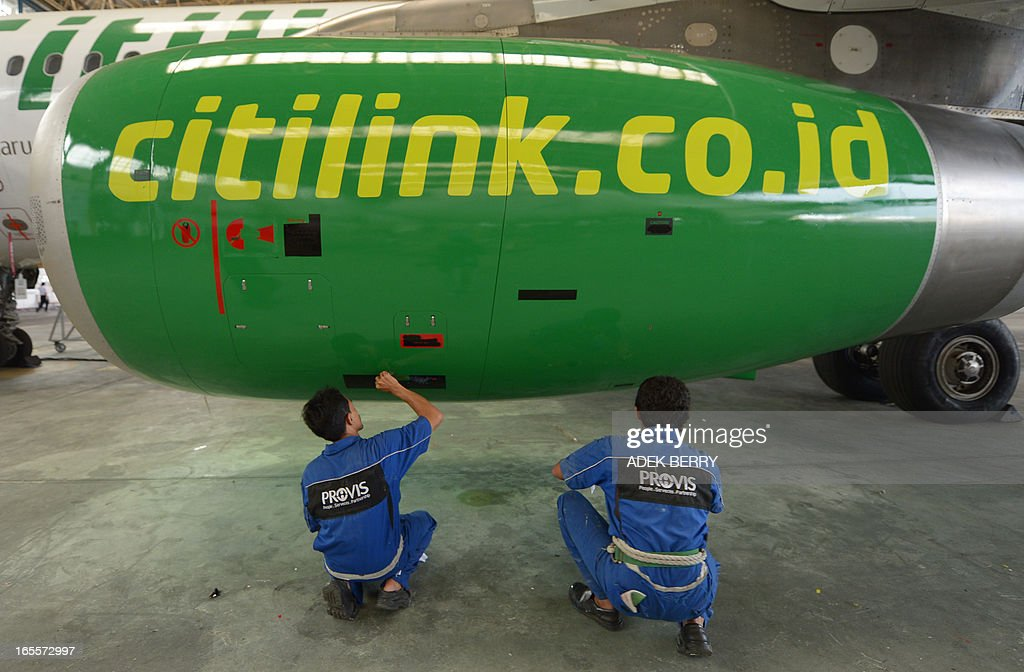 This picture taken on April 4, 2013 in Tangerang shows Indonesian technicians from GMF (Garuda Maintenance Facilities), a subsidiary of national carrier Garuda Indonesia repainting the symbol of Citilink, a low-cost carrier of Garuda Indonesia at the Sukarno-Hatta airport in Tangerang. A new rivalry between the world's biggest planemakers is heating up in Indonesia after a record deal for Airbus in a market with huge potential that until now has been a 'fortress' for Boeing. Indonesians are increasingly relying on air travel to link the archipelago of 17,000-odd islands, with up to 900 new planes set to be delivered to Indonesia in the next decade, according to the government. The potential is massive -- only six percent of Indonesians have travelled by air, according to officials, in a nation of 240 million people that has consistently clocked annual economic growth above six percent.