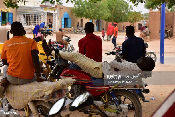 This picture taken on April 5 2017 shows motorcyle taxi riders waiting for customers in Agadez northern Niger / AFP PHOTO / ISSOUF SANOGO
