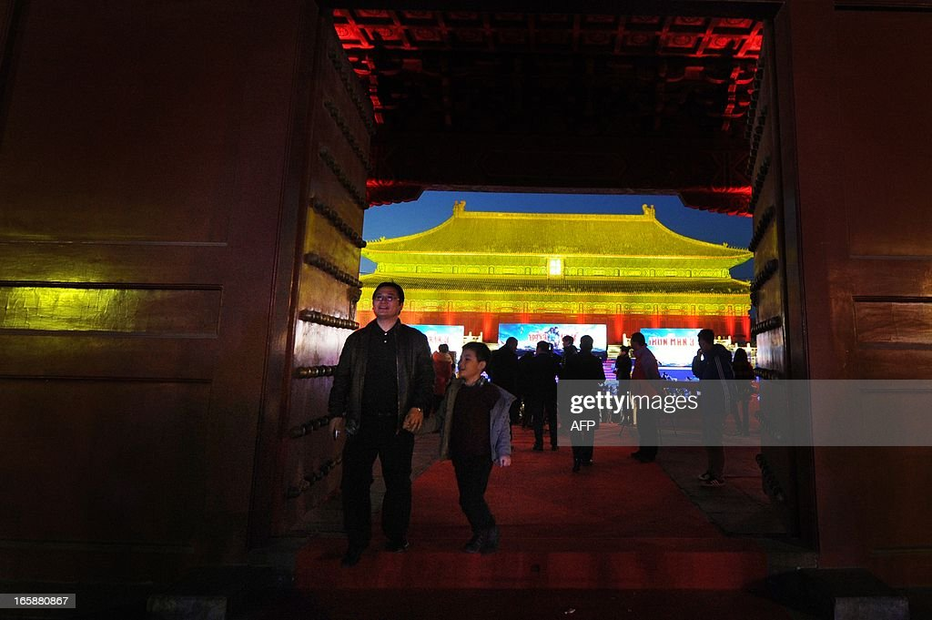 This picture taken on April 6, 2013 shows a family making their way as they attend a promotional event for the Hollywood movie ''Iron Man 3'' at the Forbidden City in Beijing.