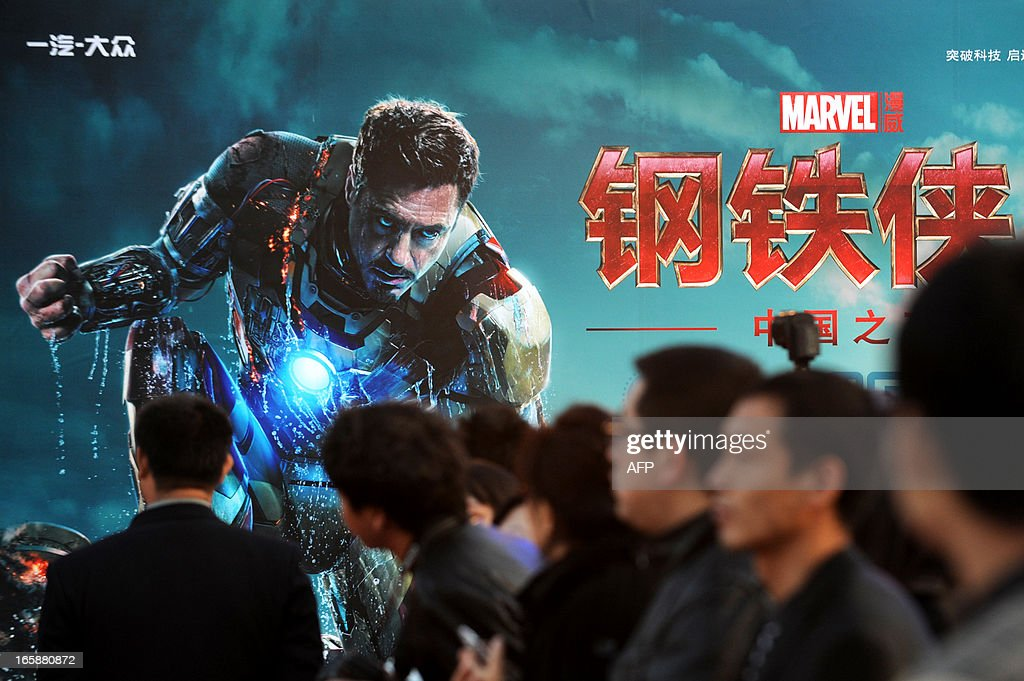 This picture taken on April 6, 2013 shows attendees sitting in front of a poster during a promotional event for the Hollywood movie ''Iron Man 3'' at the Forbidden City in Beijing.