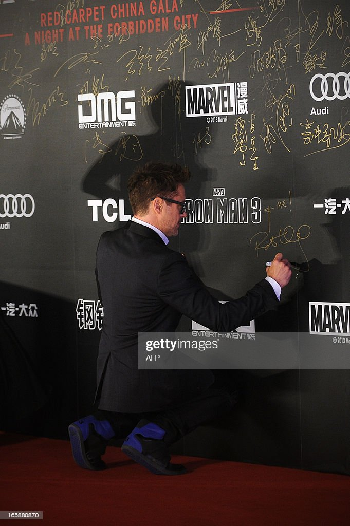 This picture taken on April 6, 2013 shows Hollywood actor Robert Downey Jr. signing a billboard during a promotional event for the movie ''Iron Man 3'' at the Forbidden City in Beijing. AFP PHOTO / WANG ZHAO