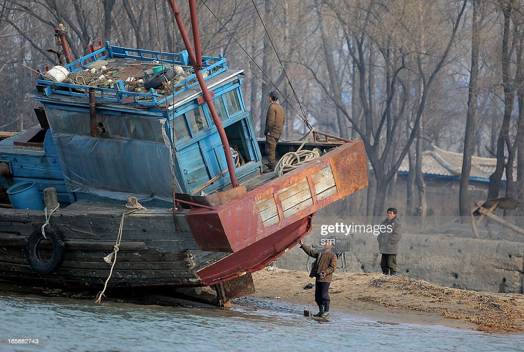 This picture taken on April 6, 2013 shows North Korean workers checking their boat on the bank of the Yalu river in the North Korean town of Sinuiju across from the Chinese city of Dandong. The US is pressuring China's new President Xi Jinping to crack down on the regime in North Korea or face an increased US military presence in the region, The New York Times reported late April 5, 2013. CHINA OUT AFP PHOTO