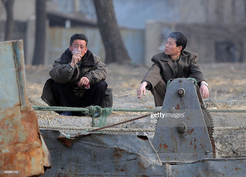 This picture taken on April 6, 2013 shows two North Korean men resting by the docks along the Yalu river in the North Korean town of Sinuiju across from the Chinese city of Dandong. The US is pressuring China's new President Xi Jinping to crack down on the regime in North Korea or face an increased US military presence in the region, The New York Times reported late April 5, 2013. CHINA OUT AFP PHOTO